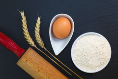 Wheat flour in white cup and organic egg decorate by wheat ear, rolling pin on black slate stone plate with copy space. For preparing baking or pasta Stock Photography