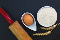 Wheat flour in white cup and organic egg decorate by wheat ear, rolling pin on black slate stone plate with copy space. For preparing baking or pasta Stock Photos
