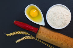 Wheat flour in white cup and organic egg decorate by wheat ear, rolling pin on black slate stone plate with copy space. For preparing baking or pasta Stock Photo