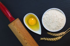 Wheat flour in white cup and organic egg decorate by wheat ear, rolling pin on black slate stone plate with copy space Stock Photography