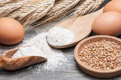 Wheat flour in a wooden spoon and eggs Royalty Free Stock Photography