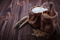 Wheat grain and flour in paper bags Royalty Free Stock Images