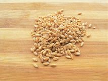 Wheat grain heap on wooden background Royalty Free Stock Images