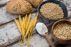 Wheat grains with bread buns, oats and spoon full of flour Stock Photo