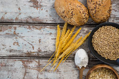 Wheat grains with bread buns, oats and spoon full of flour Royalty Free Stock Photos