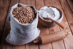 Wheat grains in burlap bag and white flour in wooden bowl and rolling pin on desk. Wheat grains in burlap bag and white flour in wooden bowl and rolling pin on Royalty Free Stock Images