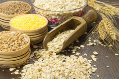 Wheat grains oats, millet, wooden spoon and a sprig of wheat on Stock Photo