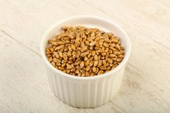 Wheat grains. In the bowl over wooden background Royalty Free Stock Photo