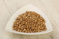 Wheat grains. In the bowl over wooden background Royalty Free Stock Images
