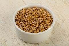Wheat grains. In the bowl over wooden background Royalty Free Stock Photography
