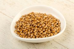 Wheat grains. In the bowl over wooden background Royalty Free Stock Photos