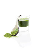 Wheat grass drink. Green wheatgrass, spirulina and chlorella juice in glass on white background with wheat grass powder on ceramic spoon. Healthy detox concept Royalty Free Stock Photography