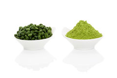 Wheat grass and spirulina. Wheat grass powder and green chlorella pills in two bowls on white background. Alternative herbal medicine. Healthy living Stock Photography