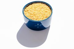 Wheat groats in a blue ceramic bowl on a white background. Close-up royalty free stock photography