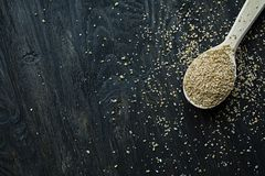 Wheat groats in a wooden spoon on a wooden dark background. Wooden spoon with wheat grains stock photo