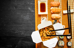 Wheat noodles with vegetables and sushi. With seafood. On a black wooden background Royalty Free Stock Images
