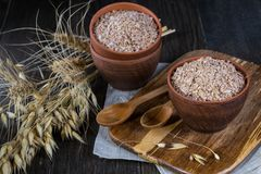 Wheat, Oat bran in clay bowl and ears of wheat and oat. Dietary supplement to improve digestion. On dark wooden background Stock Photo