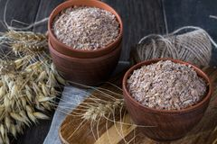 Wheat, Oat bran in clay  bowl and ears of wheat and oat.  Dietary supplement to improve digestion. On dark background Stock Image