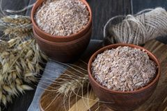 Wheat, Oat bran in clay  bowl and ears of wheat and oat.  Dietary supplement to improve digestion. On dark wooden background Royalty Free Stock Photography