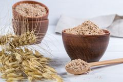 Wheat, Oat bran in clay  bowl and ears of wheat and oat.  Dietary supplement to improve digestion. On white background Stock Images