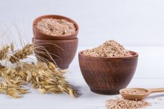 Wheat, Oat bran in clay  bowl and ears of wheat and oat.  Dietary supplement to improve digestion. On white background Royalty Free Stock Photography