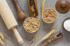 Wheat, oat grain flour in a wooden basket. Wooden spoon, rolling pin, wheat spikelets on the table Stock Images