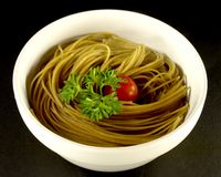 Wheat Pasta. With parsley and a tomato in a white bowl against black background royalty free stock photos