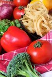 Wheat pasta. Beautiful shot of wheat pasta with different types of vegetables on wooden background Royalty Free Stock Image
