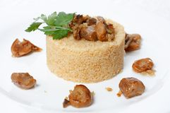 Wheat porridge with fried mushrooms. On a white plate Stock Image