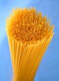 Wheat raw spaghetti closeup. On blue background Royalty Free Stock Image
