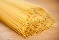 Wheat raw spaghetti closeup. On wood board Stock Photos