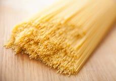 Wheat raw spaghetti closeup. On wood board Stock Photography