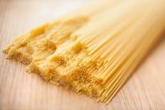 Wheat raw spaghetti closeup. On wood board Stock Photo
