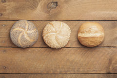 Wheat roll, poppy seed roll and sesame roll on wood Royalty Free Stock Images