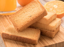 Wheat rusk in a wooden panel with orange. And orange juice Stock Photos