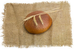Wheat rye bread and three wheat spikes on a sackcloth Stock Image
