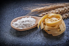 Wheat rye ears wooden spoon flour pasta on black background Stock Photography