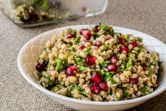 Wheat salad with pomegranate in white bowl. Stock Photos