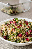 Wheat salad with pomegranate in white bowl. Royalty Free Stock Photo