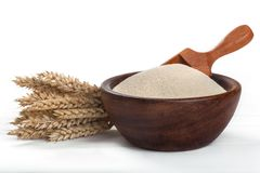 Wheat semolina. In a wooden bowl with the spoon on a white table Royalty Free Stock Photography