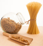 Wheat spaghetti standing tied in bundle and glass jar filled wit. H spelt pasta in the shape of fusilli Stock Photography