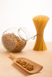 Wheat spaghetti standing tied in bundle and glass jar filled wit Stock Photography