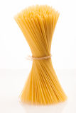 Wheat spaghetti standing tied with rope in bundle. Wheat spaghetti standing tied with rope in bundle, isolated over white background Royalty Free Stock Images