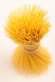 Wheat spaghetti standing tied with rope in bundle. Wheat spaghetti standing tied with rope in bundle, isolated over white background Royalty Free Stock Image