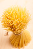 Wheat spaghetti standing tied with rope in bundle. Wheat spaghetti standing tied with rope in bundle over wooden background Stock Image