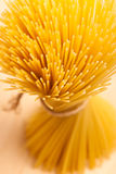 Wheat spaghetti standing tied with rope in bundle. Wheat spaghetti standing tied with rope in bundle on wooden desk Royalty Free Stock Photo