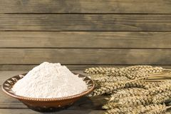 Wheat spikelets and flour on wooden plank background stock image
