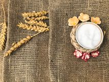 Wheat spikelets of straw and salt shaker with salt on an old brown canvas, tablecloth. Slavic symbol of welcome bread and salt. stock photography
