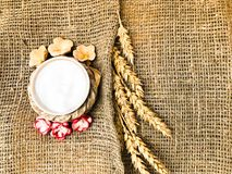 Wheat spikelets of straw and salt shaker with salt on an old brown canvas, tablecloth. Slavic symbol of welcome bread and salt. royalty free stock photo