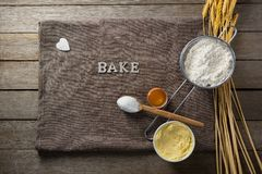 Wheat stem, wear flour, sieve, spoon placed over a cloth on wooden table Stock Images